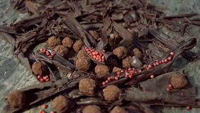 Truffles in dark chocolate with red pepper and chocolate chips. Close up refocusing shot of Composition with truffles in cocoa dust with red pepper and stock video footage