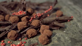Truffles in dark chocolate with red pepper and chocolate chips. Close up rotation shot of Composition with truffles in cocoa dust with red pepper and chocolate stock footage