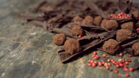 Truffles in dark chocolate with red pepper and chocolate chips. Close up sliding shot of Composition with truffles in cocoa dust with red pepper and chocolate stock video