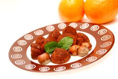 Truffles, hazelnuts, mint leaves and oranges. Hazelnuts, chocolate truffles and fresh mint leaves on a plate, and also some oranges, everything isolated on a stock images