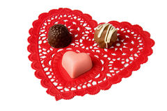 Truffles and heart  candy on red lace doily Royalty Free Stock Images