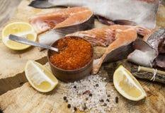Truite arc-en-ciel norvégien frais avec le caviar de citron, le sel de mer et les oignons rouges sur un fond en bois Photo stock