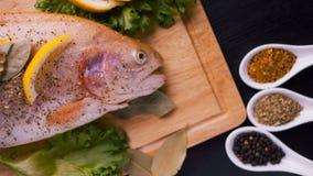 Truite fraîche et ingrédients pour préparer des plats de poisson sur la table noire Photographie stock libre de droits