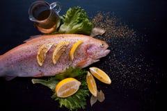 Truite fraîche et ingrédients pour préparer des plats de poisson sur la table noire, avec des épices et des cales de citron Photo libre de droits