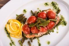 Truite grillée avec les haricots et le citron légumineux de tomates du plat blanc fin de vue supérieure  Photographie stock libre de droits