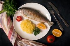 Truite, pomme de terre, citron et ail entiers grillés, fin  Photographie stock libre de droits
