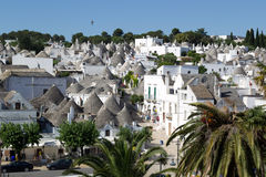 The Trulli of Alberobello is a UNESCO World Heritage site. ALBEROBELLO, PUGLIA, ITALY - JUNE 28, 2014: Tourists stroll among Trulli houses on June 28, 2014 in Royalty Free Stock Photography