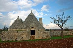 Trulli house. Assembled of rough stone on a field Stock Photography