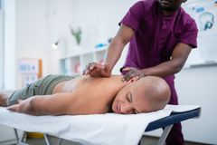 Bald man truly enjoying massage visiting therapist at weekend royalty free stock photography