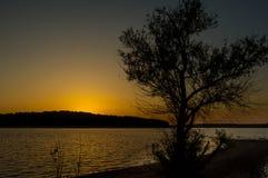 Truman与树Siloutte的湖日落 库存图片