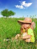Träumendes Mädchen, das im Gras sitzt Lizenzfreies Stockfoto