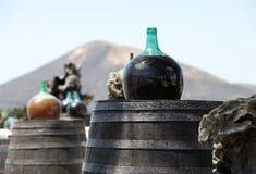 Trummor och stora flaskor med druvavin - malvasia Arkivfoton