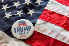 Trump-Pence 2020 campaign badge against United States flags. stock photos