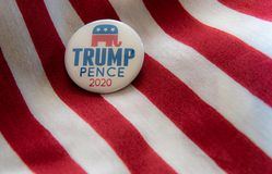 Trump-Pence 2020 campaign badge against United States flags. royalty free illustration