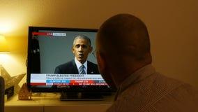 Trump President breaking news - Barack Obama speech. PARIS, FRANCE - NOV 9, 2016: Man watching tv  BBC NEWS breaking news of Obama speech after US President stock video footage