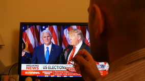 Trump President Breaking news. PARIS, FRANCE - NOV 9, 2016: Man sit down to watch TV breaking news of Trump president speech after US President Elections as stock video footage