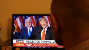 Trump President Breaking news watching tv. PARIS, FRANCE - NOV 9, 2016: Man watching TV breaking news of Trump president speech after US President Elections as stock footage