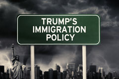 Trump`s Immigration Policy word under storm cloud. Image of green road sign with Trump`s Immigration Policy word under storm cloud stock images