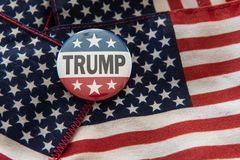 Trump 2020 stars and stripes campaign badge against United States flag. stock illustration