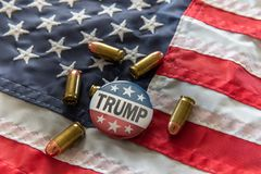 Trump 2020 stars and stripes campaign badge with bullets against United States flag royalty free illustration