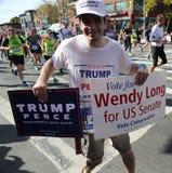 Trump supporter with political signs runs at New York City Marathon. NEW YORK - NOVEMBER 6, 2016: Trump supporter with political signs runs at New York City Royalty Free Stock Photography