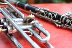 Trumpet and clarinet instruments placed on a red background stock images