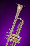 Trumpet Gold Isolated on Purple. A professional gold trumpet isolated against a spotlight purple background Royalty Free Stock Image