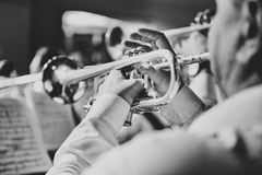 Trumpet in the hands of a musician in the band. The trumpet in the hands of the musician in the orchestra closeup in black and white Royalty Free Stock Photo