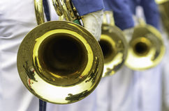 Trumpet hole. Few metal trumpets, gold and polished Stock Photos