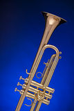 Trumpet Isolated on Blue. A gold professional trumpet isolated against a spotlight blue background with copy space Royalty Free Stock Image
