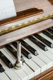trumpet mouthpiece upon the piano keys, close up Stock Image