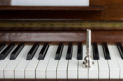 Trumpet mouthpiece upon the piano keys, close up Stock Photo