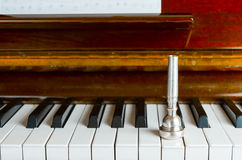 Trumpet mouthpiece upon the piano keys, close up Stock Photos