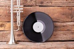 Trumpet- och vinylrekord på gammalt trä fotografering för bildbyråer