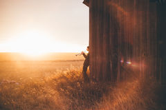 Trumpet player by barn at sunset Stock Photos