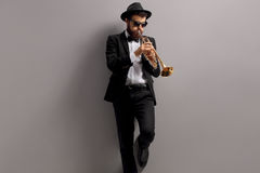 Trumpet player leaning against a wall. Trumpet player leaning against a gray wall Royalty Free Stock Image