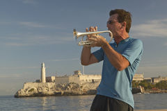 A trumpet player playing music in front of Castillo del Morro, El Morro Fort, across the Havana channel, Cuba Stock Photos