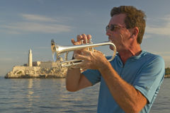 A trumpet player playing music in front of Castillo del Morro, El Morro Fort, across the Havana channel, Cuba Royalty Free Stock Image