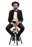 Trumpet player sitting on a chair. And looking at the camera isolated on white background Royalty Free Stock Images