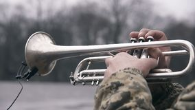 Trumpet playing street musician. Trumpet playing street musician with military camouflage coat stock footage