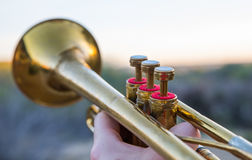 Trumpet Pointed Skyward. Shot of a brass trumpet pointed upward in a playing position at sunset stock photos
