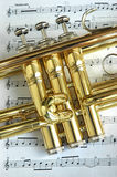 Trumpet Valves. On musiacl notes background Royalty Free Stock Photos