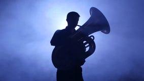 Trumpeter στο επίκεντρο στα καπνώδη παιχνίδια στούντιο στο tuba closeup φιλμ μικρού μήκους