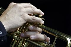 Trumpeter. Caucasian trumpeters hands on keys against black background Stock Images