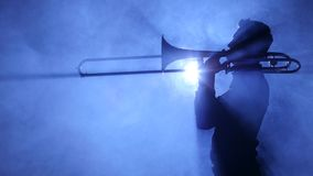 Trumpeter man in spotlight in smoky studio plays on trombone stock video footage