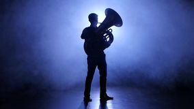 Trumpeter man in spotlight in smoky studio plays on tuba stock footage