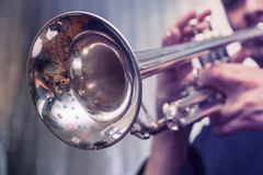Trumpeter is playing on a silver trumpet stock image