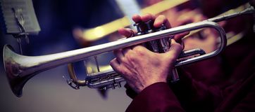 Trumpeter plays his trumpet in the band during live concert Stock Photos