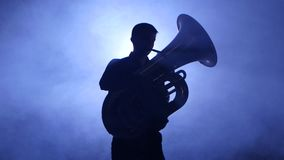 Trumpeter in spotlight in smoky studio plays on tuba. Closeup stock footage