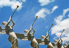 Trumpeting Angels. Angels with trumpets aiming towards heaven with the sky in the background Stock Photography